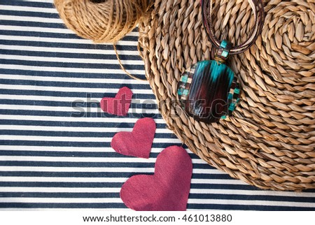 Pendant and hearts on striped fabric. Handmade jewelry of polymer clay. Unique gift. Valentine day.