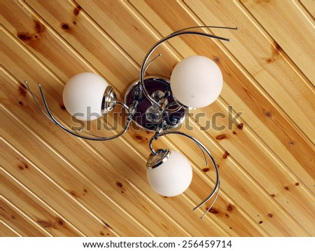 Pendant lamp with three bulbs on wooden ceiling    - stock photo