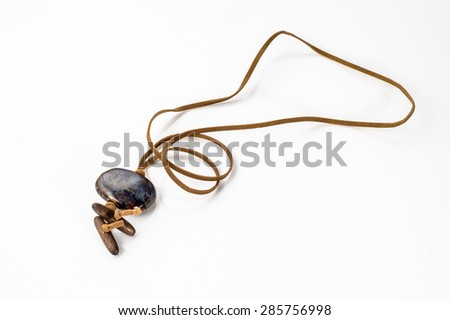 Pendant made with ceramics bead and leather straps isolated on a white background. Handmade jewelry. - stock photo