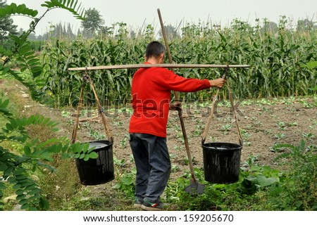PENGZHOU, CHINA:  Farmer carrying two plastic pails filled with water using a shoulder yoke