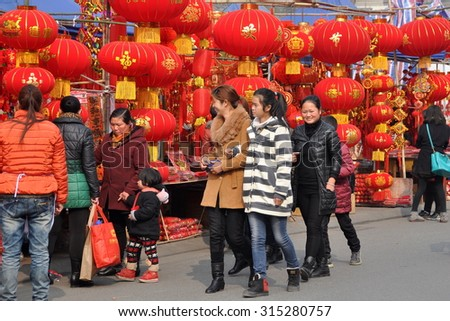 Pengzhou, China - January 23, 2014:  People shopping for Chinese Lunar New Year holiday decorations at the Long Xing outdoor marketplace