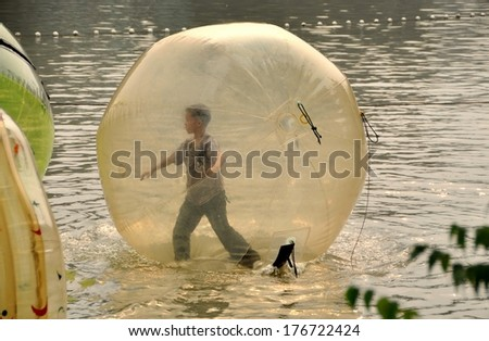 PENGZHOU, CHINA - NOV 6, 2009:  A little boy playing inside a giant inflated plastic balloon on the lake in Pengzhou City Park