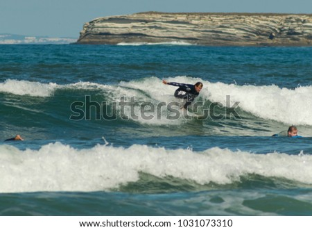 PENICHE, PORTUGAL - September 22, 2016: Recreational surfer rides a wave off Gamboa Beach in Peniche, Portugal.