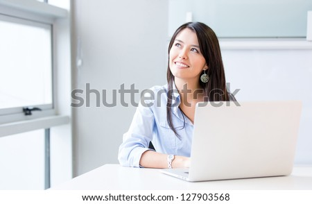 Penisve businesswoman working at the office on a laptop - stock photo