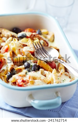 Penne baked with cherry tomatoes, olives and cheese sauce - stock photo