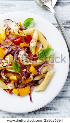 Penne pasta baked with peppers, red onion and mozzarella  - stock photo