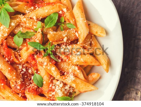 Penne pasta in tomato sauce with basil and parmesan cheese on rustic wooden background.  - stock photo