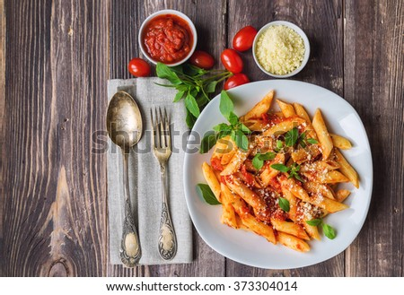 Penne pasta in tomato sauce with basil parmesan cheese on rustic wooden background - stock photo
