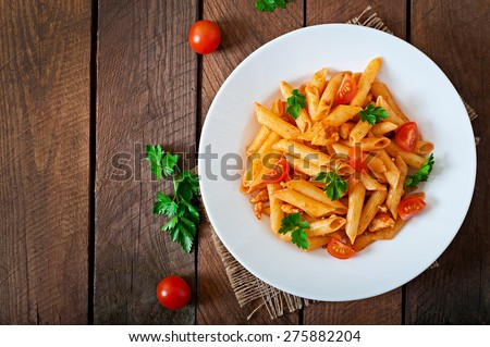 Penne pasta in tomato sauce with chicken, tomatoes decorated with parsley on a wooden background - stock photo