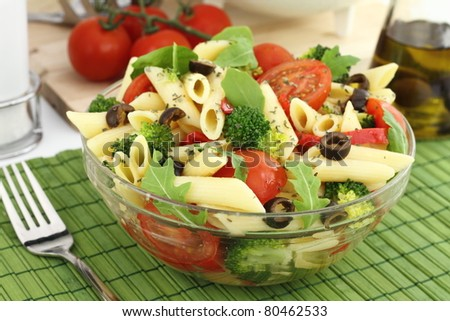 Penne pasta salad with vegetables and herbs - stock photo