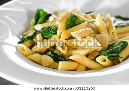 Penne pasta with a creamy sauce with parmesan cheese and basil on a white plate on a wood background isolated. Penne pasta with blue cheese sauce and spinach.   - stock photo