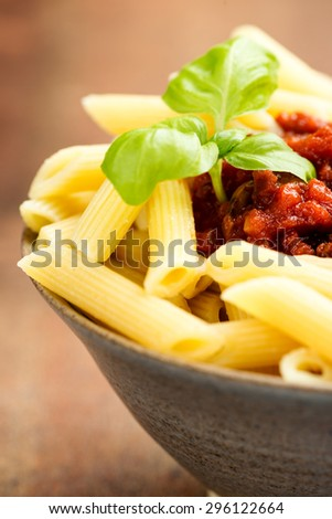Penne pasta with a tomato bolognese beef sauce on the table