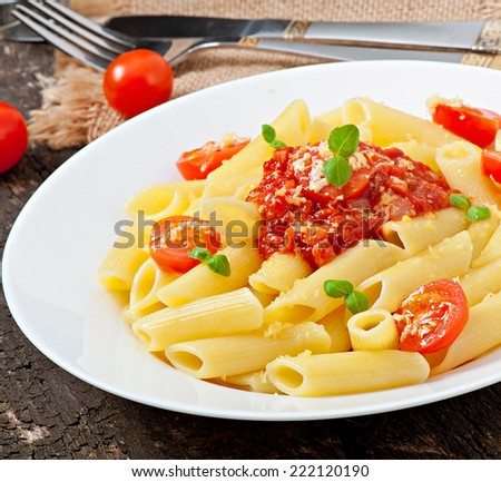 Penne pasta with bolognese sauce, parmesan cheese and basil - stock photo