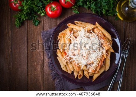 Penne pasta with chicken, tomato sauce and parmesan cheese on dark wooden background top view. Italian cuisine. Space for text. - stock photo