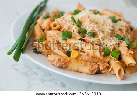 Penne pasta with healthy tuna fish, cheese and chopped scallion or spring onion leaves. Served on a white oval plate - stock photo