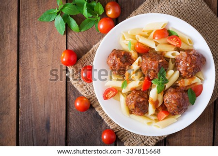 Penne pasta with meatballs in tomato sauce in a white bowl. Top view - stock photo