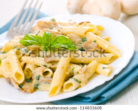 Penne pasta with mushroom and basil - stock photo