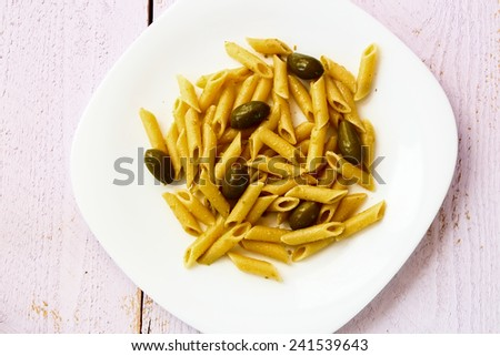 Penne pasta with pesto and olives on white wooden background. Top view.