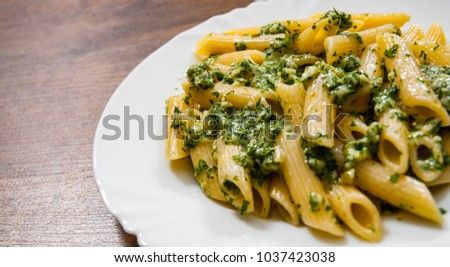 penne pasta with pesto sauce in plate on a wooden background.