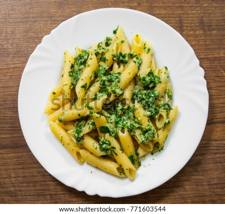 penne pasta with pesto sauce in plate on a wooden background. top view