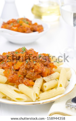penne pasta with sauce of beef, tomato and pumpkin on the plate close-up and dressing in the background, vertical