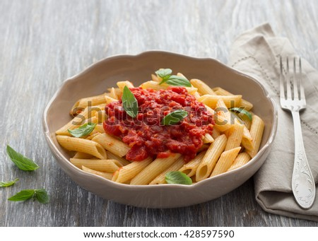 Penne pasta with tomato sauce and basil on the wooden table - stock photo