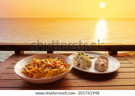penne pasta with tomato sauce and chicken steak during sunset. - stock photo