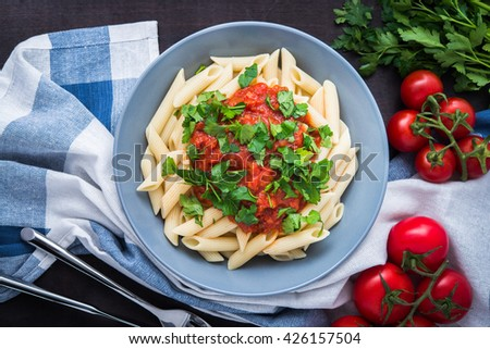 Penne pasta with tomato sauce and parsley on dark wooden background top view. Italian cuisine. - stock photo