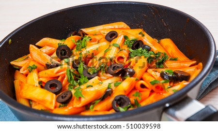 Penne pasta with tomato sauce in a frying pan