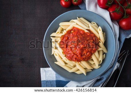Penne pasta with tomato sauce on dark wooden background top view. Italian cuisine. - stock photo