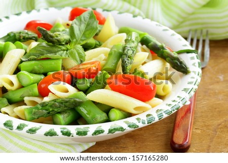 penne pasta with tomatoes and asparagus, fresh spring food - stock photo