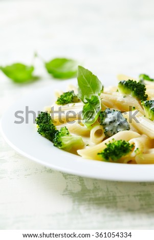 Penne with cheese sauce and broccoli - stock photo