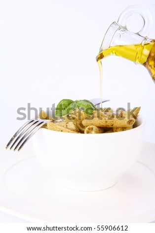 Penne with pesto with olive oil being poured onto it