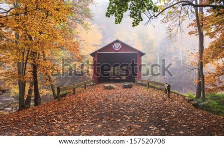 Pennsylvania foggy autumn landscape Josiah Hess red covered bridge spanning Huntington Creek in Orangeville.  The historic bridge is one of the stops on the annual Covered Bridge Festival. - stock photo