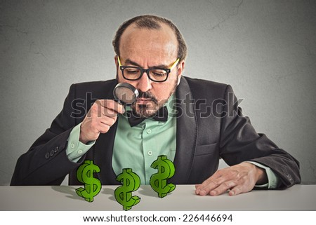 penny pincher. Business man looking through magnifying glass at dollar signs symbol on table isolated grey wall office background. Economy financial wealth success concept. Ponzi scheme investigation  - stock photo