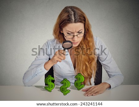 penny pincher. Business woman looking through magnifying glass dollar signs symbol on table isolated grey wall office background. Economy financial wealth success concept. Ponzi scheme investigation - stock photo