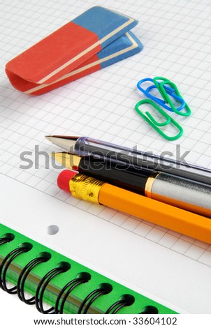 Pens, pencil and erasers on a notebook