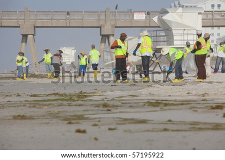 PENSACOLA BEACH - JULY 7: oil workers continue to clean the beach of oil on July 7, 2010 in Pensacola Beach, FL.