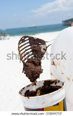 PENSACOLA BEACH - 23 JUNE:  A beachgoer collects sticky oil covered sand on June 23, 2010 in Pensacola Beach, FL. - stock photo