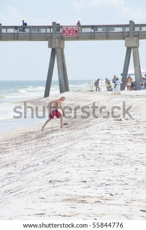 PENSACOLA BEACH - JUNE 23:  A beachgoer steps over oil patches on June 23, 2010 in Pensacola Beach, FL. BP oil workers attempt to clean the beach area in the background. - stock photo