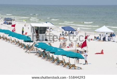 PENSACOLA BEACH - 23 JUNE:  A long row of deserted beach lounge chairs is shown on June 23, 2010 in Pensacola Beach, FL. - stock photo