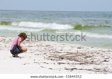 PENSACOLA BEACH - JUNE 23:  An unidentifed beachgoer crouches next to oil covered sand on June 23, 2010 in Pensacola Beach, FL. - stock photo