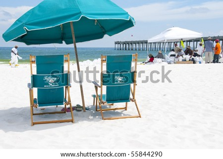 PENSACOLA BEACH - JUNE 23:  Beach chairs lie empty on June 23, 2010 in Pensacola, FL. BP oil workers work in the background. - stock photo