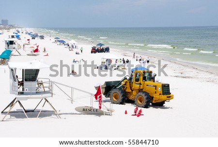 PENSACOLA BEACH - JUNE 23:  BP oil workers and heavy machinery work to clean oil covered sand on June 23, 2010 in Pensacola Beach, FL. - stock photo