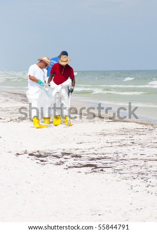 PENSACOLA BEACH - JUNE 23: BP oil workers attempt to clean the beach of oil on June 23, 2010 in Pensacola Beach, FL. - stock photo