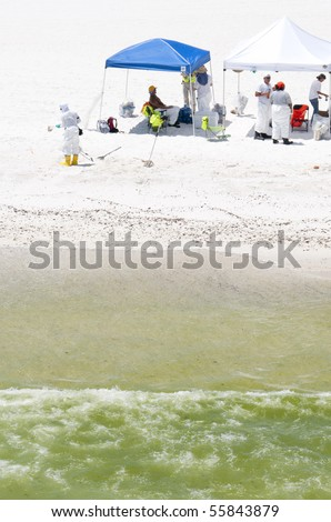 PENSACOLA BEACH - 23 JUNE:  BP oil workers attempt to remove oil washed ashore Pensacola Beach, FL on June 23, 2010. - stock photo