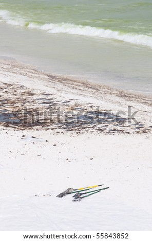 PENSACOLA BEACH - JUNE 23:  Oil covered sand is shown on June 23, 2010 in Pensacola Beach, FL. BP worker shovels lie in the foreground. - stock photo