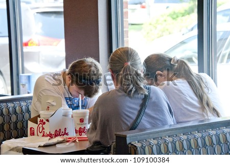 PENSACOLA, FL - AUGUST 1: Patrons pray at Chick-Fil-A restaurant in Pensacola, FL, on August 1, 2012 on national Day of Support following backlash from the owner supporting traditional marriage. - stock photo