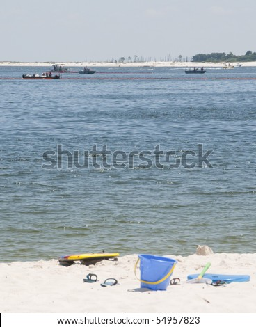 PENSACOLA - JUNE 10:  Beach toys lie on the beach as BP oil spill workers (background) try to protect the beach area of Naval Air Station Pensacola as oil washes ashore on June 10, 2010 in Pensacola, FL. - stock photo