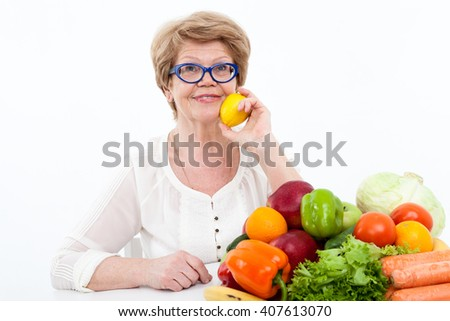 Pension age woman touching lemon to cheek, fresh fruit and vegetables on table, isolated on white background - stock photo